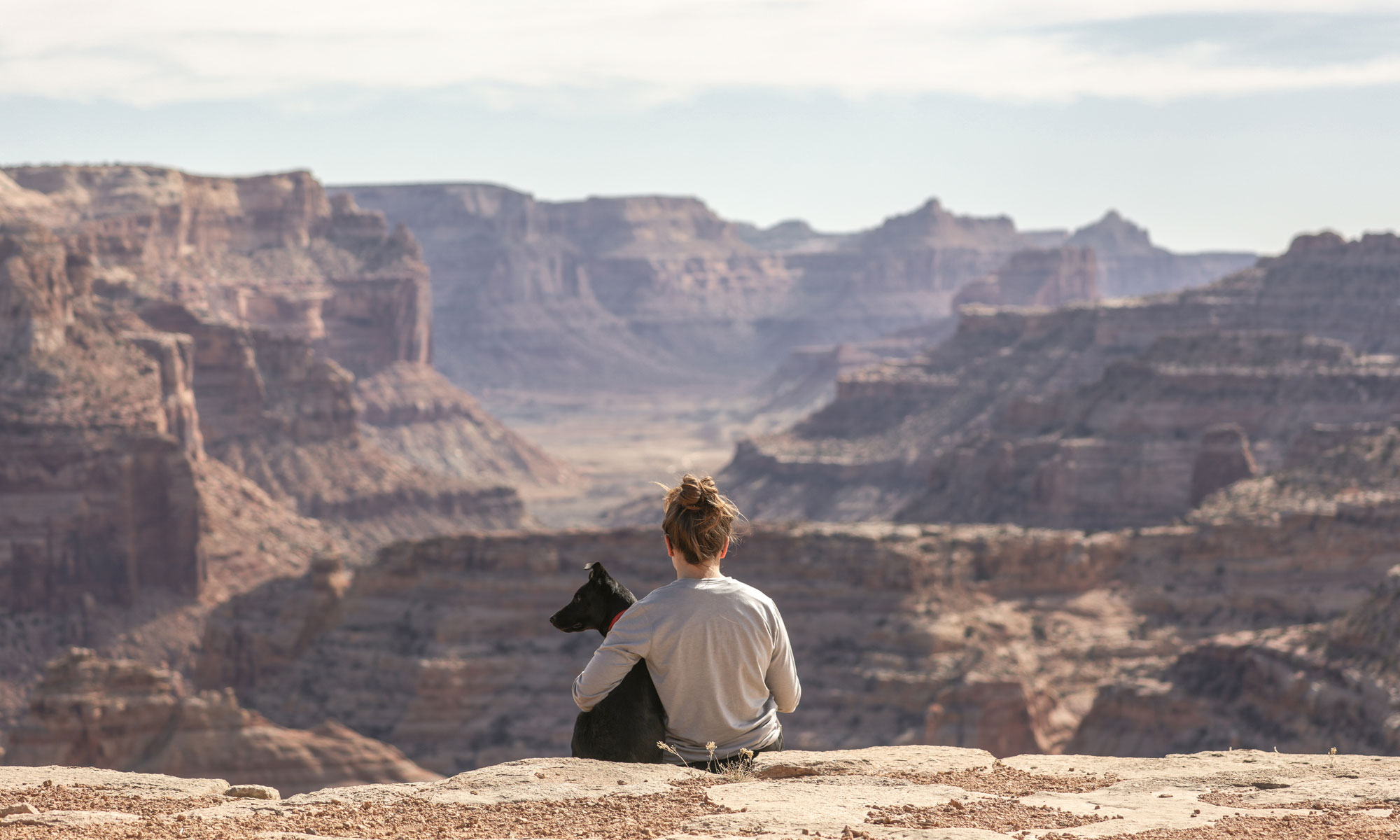 Empathy: Woman sitting with dog at Grand Canyon