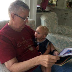 Man reading to his grandchild